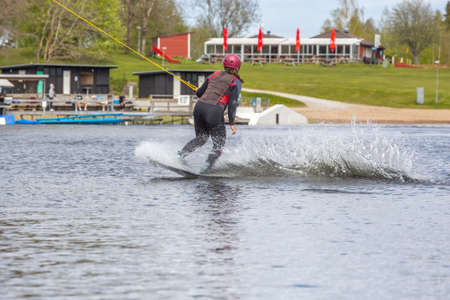 Fagersta, Sweden - Maj 26, 2020: Young wakeboarder rides a wakeboard on the lake. Wakeboarding is cool, extreme sport Redactioneel
