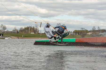 Fagersta, Sweden - Maj 01, 2020: Two teenagers wakeboarders on a lake during a physical education lesson. makes an extreme jump on wakeboarding, around there are a lot of splashes