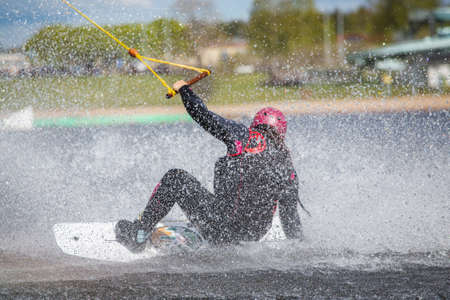 Fagersta, Sweden - Maj 26, 2020: Teen Wakeboarder on wakeboard landed in water surrounded by spray. Wakeboarding is an extreme sport.