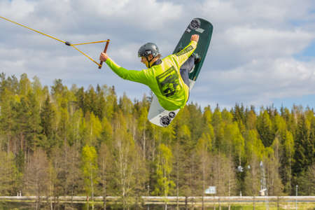 Fagersta, Sweden - Maj 26, 2020: Wakeboarding. Teen Wakeboarder makes extremely difficult jump in air on wakeboard. Guy flies in the sky