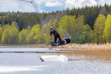 Fagersta, Sweden - Maj 18, 2020: Teenager boy wakeboarders on a lake during a physical education lesson Redactioneel