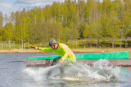 Fagersta, Sweden - Maj 26, 2020: Wakeboarder on wakeboard landed in water surrounded by spray. Wakeboarding is an extreme sport. Redactioneel