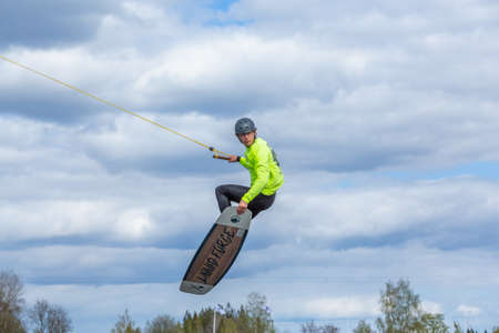 Fagersta, Sweden - Maj 26, 2020: Wakeboarding. Teen Wakeboarder makes extreme jump in air on wakeboard and looks at the camera. Guy flies in the sky