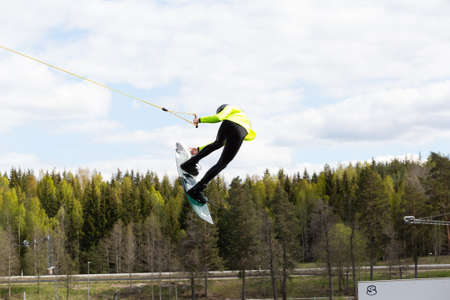 Fagersta, Sweden - Maj 26, 2020: Wakeboarding. Teen Wakeboarder makes extreme Jump in air on wakeboard. Guy flies in the sky