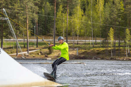Fagersta, Sweden - Maj 26, 2020: Guy is riding a wakeboard on the lake. Wakeboard is Extreme Sports Redactioneel