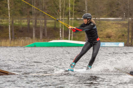 Fagersta, Sweden - Maj 07, 2020: girl teenager wakeboarders on a lake during a physical education lesson. Girl is getting ready to jump