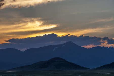 Beautiful blue ridge mountain sunset with orange sky in Mongolian Altai.