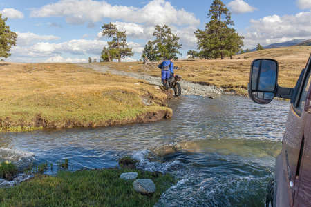 Altai, Mongolia - June 14, 2017: A motorcyclist pushes a motorcycle along a road flooded with water. Altai, Mongolia Redactioneel