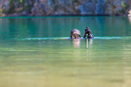 the diver plunges into the water, looks into the camera. Head on the surface