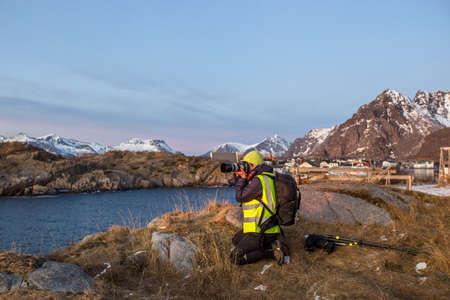Lofoten, Norway- Mars 12 2020: Photographer woman photographs the Norwegian fjords during sunset time.