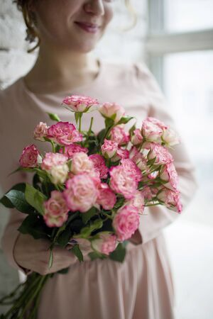 magenta dress: woman in pink dress holding a bouquet of pink garden roses Stock Photo