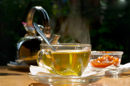exhalation: Cup of tea, jam and teapot on a table on open air