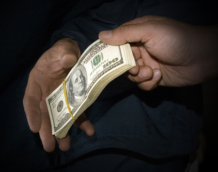 tonality: Transfer of money from hands in hands in the dark tonality, symbolizing a bribe.