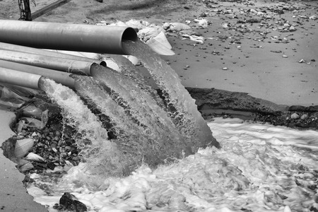 water flowing: Waste water is drained from the pipe into the sea.