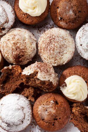chocolate powder: Baked homemade cupcakes with cream, sugar and chocolate powder