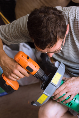 electric trimmer: The man fastens to the screwdriver parts trimmer for grass