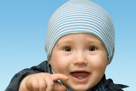 ojos azules: El niño riendo mostrando en usted por un dedo índice Foto de archivo