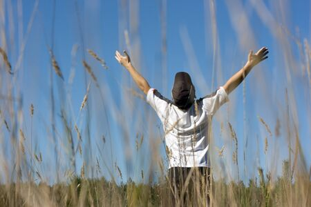 hands lifted: The teenager, with the hands lifted to the sky on a summer meadow Stock Photo