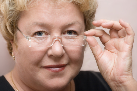 senior female: Kind sight of the woman because of glasses Stock Photo