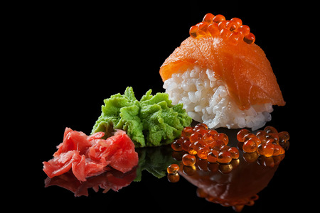 Sushi con caviar rojo, wasabi, jengibre en el fondo de cristal negro