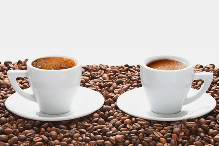 Two cups of hot coffee with foam in scattering of coffee beans on white background