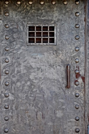 Metal door with handle, rivets and a grate, as in prison Stock Photo - 7348456