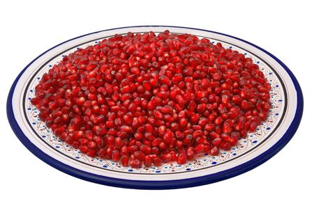 Grains of pomegranate on a traditional Tunisian plate, isolated