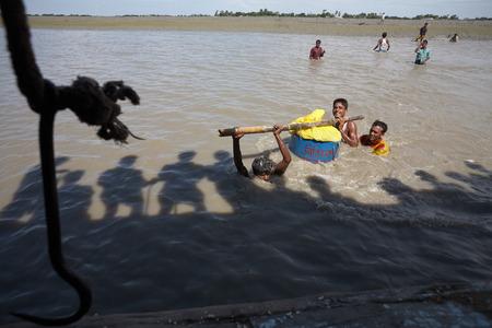 Chittagong, Bangladesh, July 2009. Loading a boat after Cyclone Sidr. Editöryel