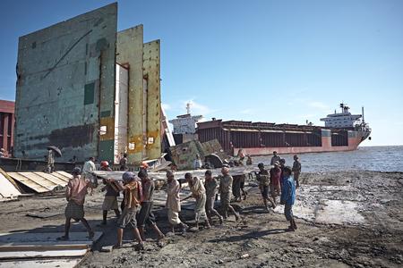 Chittagong, Bangladesh, July 2009. Men at work scrapping ships by hand.