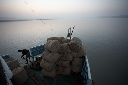 Bangladesh, January 2008. Cargo ship in the delta of the Ganges River at dawn.