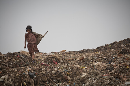 New Delhi, India, July 2009.Girl in a garbage dump outside the city. Stock Photo - 108280051