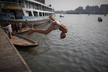 Dhaka, Bangladesh, January 2008. A young man throws himself headlong into the water in the Sadarghat launch terminal.