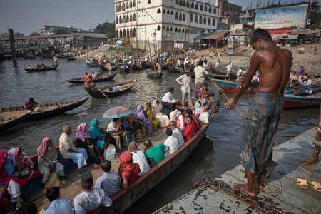 Dhaka, Bangladesh, July 2009. Passengers and rowers on the rowboats at the Sadarghat launch terminal.