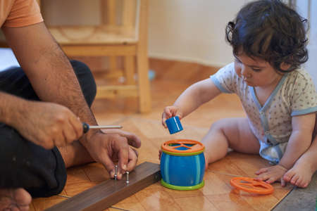 Father screws wood and his baby helps him. Assembling a piece of furniture at home. Parenting session