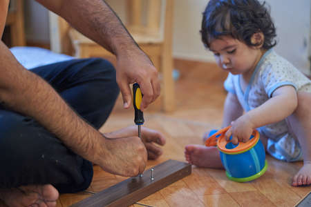 Father tries to assemble desk with baby playing. Assembling furniture at home. Parenting session