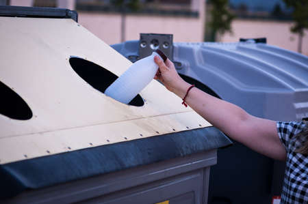 woman hand recycling plastic bottle into yellow container and unfocused gray container, horizontal format