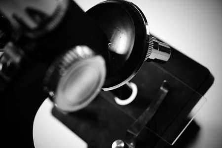 macro image of microscope to view defocused black covid 19 virus with focus on silver lenses Archivio Fotografico