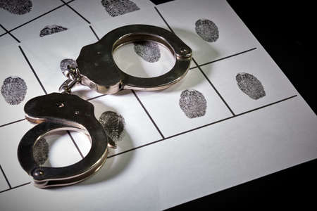 silver police handcuffs on police sheet with suspect fingerprints, horizontal format