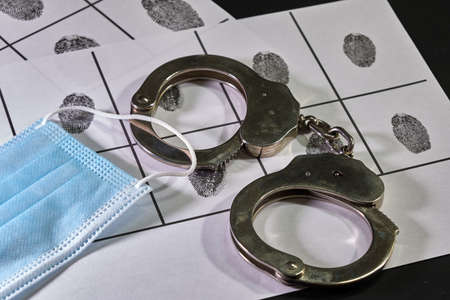 silver police handcuffs on police sheet with suspect fingerprints and mask for covid19, horizontal format