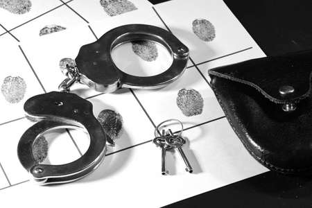 silver police handcuffs with their keys and black leather case on police sheet with suspect fingerprints, horizontal format