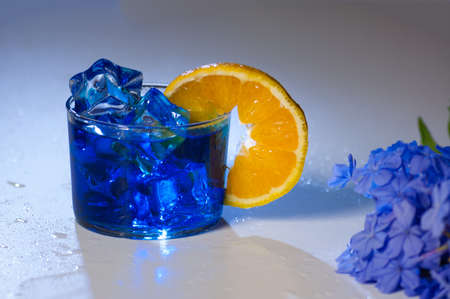 blue mojito cocktail with orange slice on a white table, horizontal format