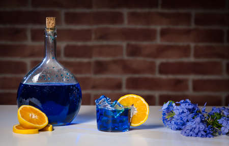 glass bottle with blue mojito cocktail on top of a white table with oranges and blue flowers blur brick background, horizontal format