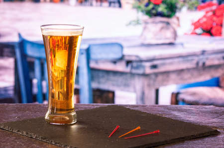 glass of ice cold beer on black slate base on bar deck with unfocused blue and white wooden chairs