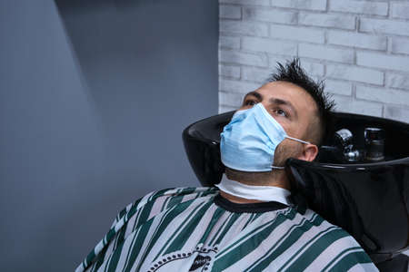 young person in hairdresser washing head and hair with face mask on, horizontal format 免版税图像
