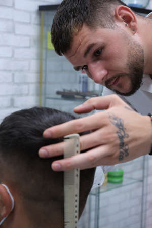 closeup of tattooed face and hands of young bearded hairdresser with white comb, horizontal format