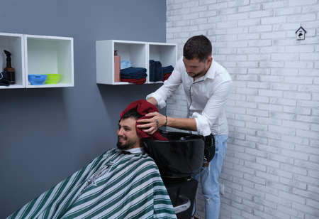 Young barber drying hair with red towel to happy bearded person, horizontal format