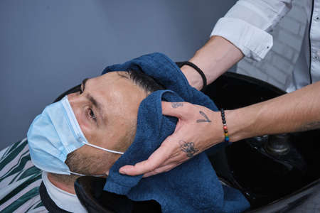 Young barber drying hair with blue towel to happy bearded person, horizontal format