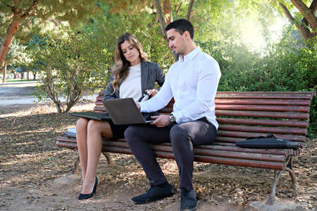 Young businesswoman negotiating with executive man on park bench