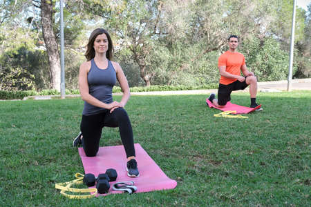 young sports couple doing muscle stretching exercises in a park with grass. Sport fitness concept