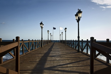 A wood pier on a beach of Marbella (Costa del Sol), Spain photo